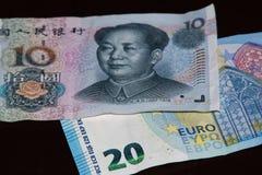 Ten Chinese yuan above twenty euro banknote. Ten Chinese yuan is above twenty euro banknote on black background royalty free stock image
