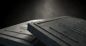 The Ten Commandments. Two representative stone tablets with the ten commandments inscribed on them on an isolated dark ethereal background Stock Photos