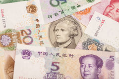 Ten dollar bill surrounded by Chinese Yuan Stock Photo