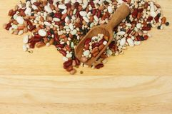 Ten bean mix and scoop. Ten dried bean mix with a wooden scoop on a chopping board with copy space below Stock Image