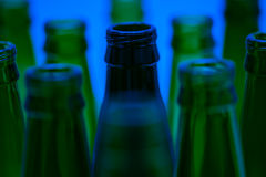 Ten empty beer bottles shot with blue light. Stock Image