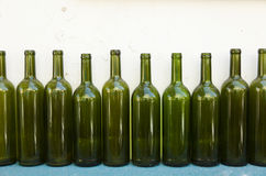 Mediterranean Bottles. Ten empty green wine bottles in a row on the background of old run-down white wall, resting on turquoise wooden surface Stock Images