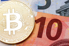 Ten euro banknote as a background for golden bitcoin. High resolution photo Stock Image
