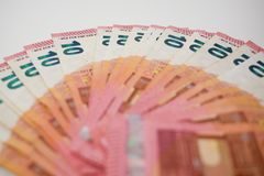 Ten Euro banknotes fanned out on a white desk, oblique angle view with shallow depth of field stock images