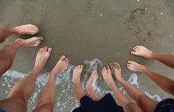 Ten feet of a family of five persons. On the beach in summer stock photos
