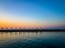Ten gazebos on the pier. Blue sky, calm water and evening sunset stock photos