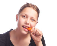 Ten girl eating carrot Stock Images