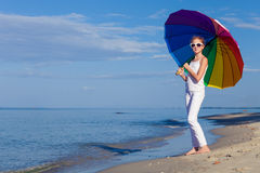 Ten girl with umbrella standing on the beach Stock Image