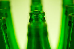 Ten green bottles in three rows shot with green light. Royalty Free Stock Image