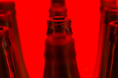 Ten green bottles in three rows shot with red light. Royalty Free Stock Image