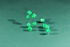 Ten green dices falling on a green table. Ten green dices falling on a isolated green table royalty free stock images