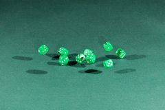 Ten green dices falling on a green table. Ten green dices falling on a isolated green table royalty free stock photos