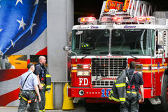 Ten house fire station in NY. New York City, USA - May 19, 2014: Four firefighters and a fire truck in front of the fire station of the 'Ten House' near 9/11 Royalty Free Stock Photo