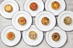 Ten quiches on white plates. Ten individual mini quiches on white enamel plates on a light coloured table tops royalty free stock images