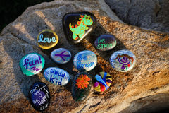 Ten painted rocks on a boulder. Ten inspirational words or quotes painted on small rocks are on a boulder in nice light.  Rocks are yard or garden art and have Stock Images