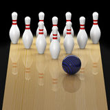 Ten pin bowling in action. Ten pin bowling lane with blue ball in action about to strike on black background Stock Photo