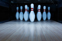 Ten pin bowling alley background. Closeup of tenpin row on a lane, night light Stock Image