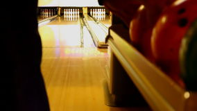 Ten pin bowling ball strike. Man picks an orange bowling ball and bowls a strike knocking down all ten pins stock footage
