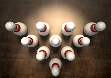 Ten Pin Bowling Pins. An arrangement of white and red used vintage bowling pins resting on a wooden bowling alley surface on a dark background Royalty Free Stock Image