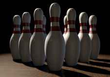 Ten Pin Bowling Pins. An arrangement of white and red used vintage bowling pins resting on a wooden bowling alley surface on a dark background Royalty Free Stock Photos