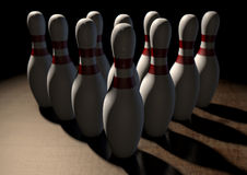 Ten Pin Bowling Pins. An arrangement of white and red used vintage bowling pins resting on a wooden bowling alley surface on a dark background Stock Image
