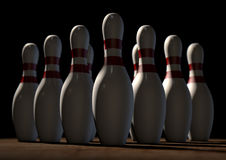 Ten Pin Bowling Pins. An arrangement of white and red used vintage bowling pins resting on a wooden bowling alley surface on a dark background Stock Photo