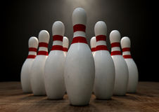Ten Pin Bowling Pins. An arrangement of white and red used vintage bowling pins resting on a wooden bowling alley surface on a dark background Royalty Free Stock Photography