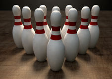 Ten Pin Bowling Pins. An arrangement of white and red used vintage bowling pins resting on a wooden bowling alley surface on a dark background Stock Photos