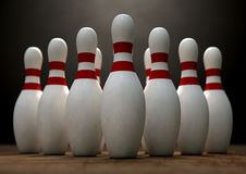 Ten Pin Bowling Pins. An arrangement of white and red used vintage bowling pins resting on a wooden bowling alley surface on a dark background Royalty Free Stock Images