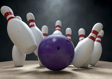 Ten Pin Bowling Pins And Ball. An arrangement of white and red used vintage bowling pins being struck by a bowling ball on a wooden bowling alley surface on a Royalty Free Stock Photography