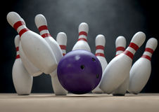 Ten Pin Bowling Pins And Ball. An arrangement of white and red used vintage bowling pins being struck by a bowling ball on a wooden bowling alley surface on a Stock Photo