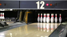 Ten-pin bowling wood-structure lane. Bowling ball rolling the lane and knocking down pins stock video