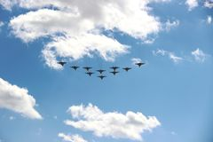 Ten planes in a blue sky with clouds on a Sunny day. A group of ten aircraft in a blue sky with white clouds. stock photography