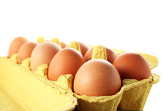 Ten raw chicken eggs in a carton. Ten raw chicken eggs in a yellow carton. Focus is selectively on the first egg Royalty Free Stock Images