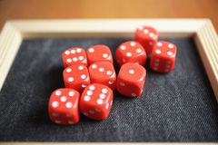Ten red dice on a black table Royalty Free Stock Image