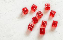Ten red transcluent craps dices showing different numbers on white marble board, space for text left side royalty free stock photo