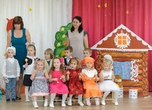 Ten small children dressed in carnival costumes and women. BALASHIKHA, RUSSIA - OCTOBER 26: Ten small children, dressed in carnival costumes, and two adult women Royalty Free Stock Photo