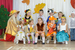 Ten small children and adult woman dressed in carnival costumes Royalty Free Stock Image