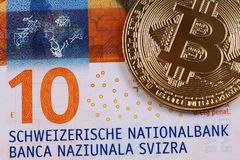 Ten Swiss Franc bank note with a golden bitcoin. A close up image of a golden bitcoin with a ten Swiss Franc bank note royalty free stock image