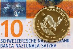 Ten Swiss Franc note with a gold Krugerrand one ounce coin. A macro image of a ten Swiss Franc bank note with a one ounce Krugerrand coin royalty free stock photos