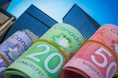 Canadian Dollars on skyscraper and blue sky background. Ten, twenty and fifty Canadian Dollars money rolls on clear blue sky and skyscraper background Stock Image