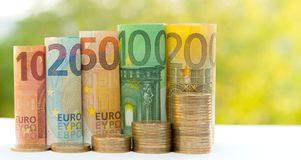 Ten, twenty, fifty, one hundred, two hundred and coins euro roll. Ed bills banknotes on green blurred bokeh background. Histogram from the euro. Concept of Stock Photos