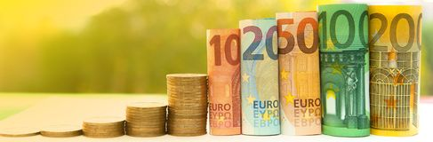Ten, twenty, fifty, one hundred, two hundred and coins euro roll. Ed bills banknotes on green blurred bokeh background. Histogram from the euro. Concept of Royalty Free Stock Image