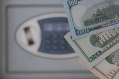 Ten, twenty and one hundred dollars on a blurred background of a safe deposit box. Selective focus. The concept of storing money. Ten, twenty and one hundred US stock image
