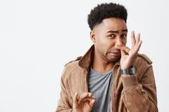 Ten wącha naprawdę bad Zamyka w górę portreta młody śmieszny ciemnoskóry mężczyzna z afro fryzury przymknięcia nosem z palcami obrazy royalty free