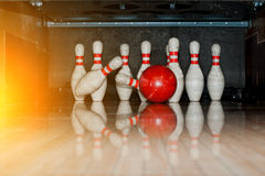 Ten white pins in a bowling alley with ball hit Royalty Free Stock Image