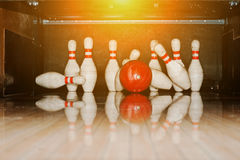 Ten white pins in a bowling alley with ball hit Royalty Free Stock Photography