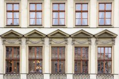 Ten Windows on the facade of the old vintage beige house.  Royalty Free Stock Images