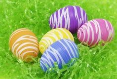 Grupa Easter jajka siedzi na zielonej plastikowej trawie Obraz Royalty Free