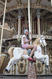 Ten-year girl riding a classic French carousel.  Десятил Stock Photo